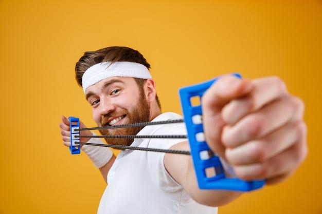 Starker athletischer kerl sportmann, der expander auf orange streckt