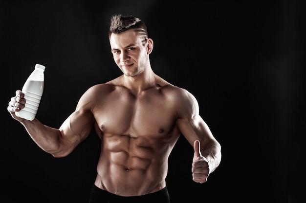 Starker athletischer muskulöser mann, der flasche hält