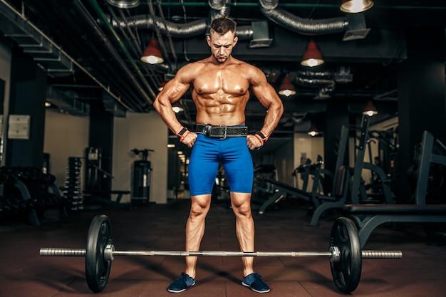 Starker bodybuilder, der für kreuzheben der hantel sich vorbereitet