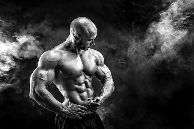 Starker bodybuilder, der muskeln aufwirft und zeigt