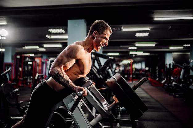 Starker bodybuilder, der schwergewichts- übung für rückseite auf maschine tut. t-pull-übung