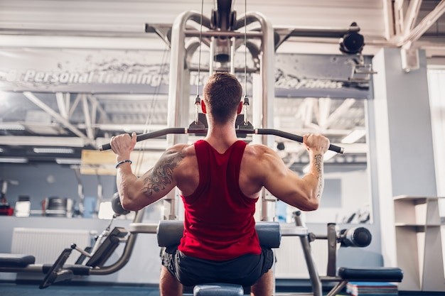 Starker bodybuilder, der schwergewichts- übung für rückseite auf maschine tut