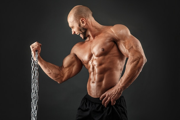 Starker bodybuilder, der übung mit metallkette macht