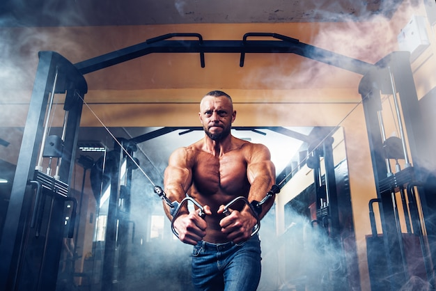 Starker bodybuilder, der übungen an der turnhalle tut