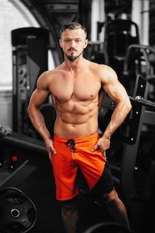 Starker bodybuilder sieht gerade aus, muskulöser bodybuilder gutaussehende männer, die übungen im fitnessstudio machen