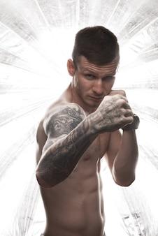 Starker boxerstand der tätowierung vor dunklem hintergrund