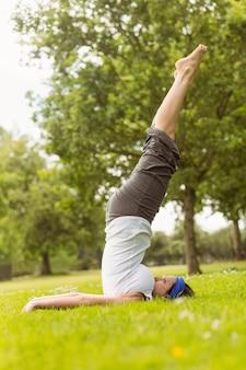 Starker brunette, der yoga auf gras tut