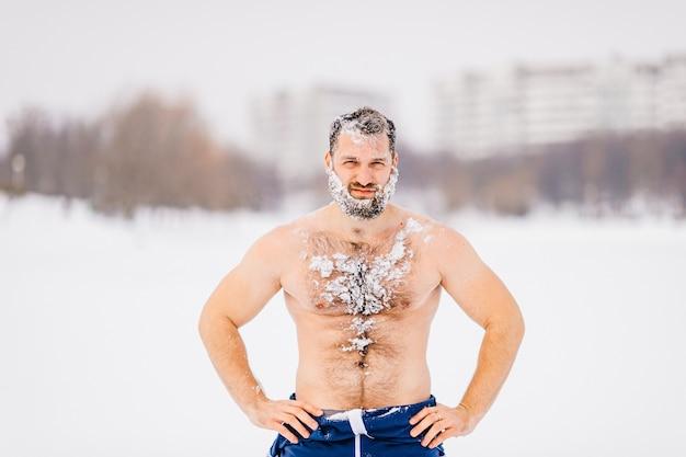 Starker brutaler nackter mann mit bart im schnee, der draußen aufwirft