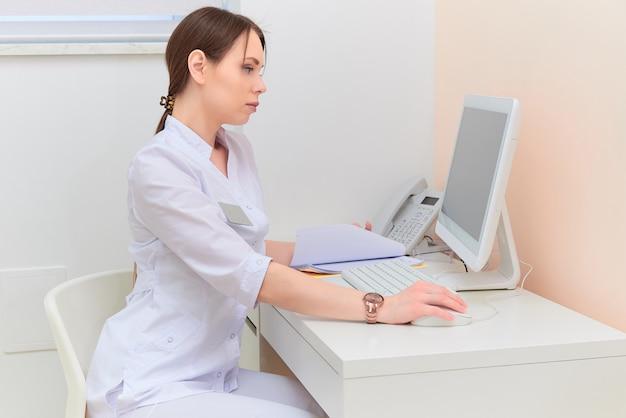 Starker doktor mit dem bericht, der computermonitor am schreibtisch im ärztlichen dienst betrachtet.