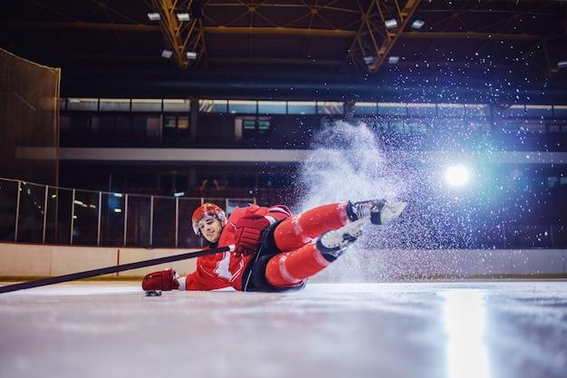 Starker eishockeyspieler, der auf eis fällt, um puck vom teamkollegen zu erhalten.