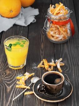 Starker espresso, frisch gepresster orangensaft mit minzblättern und hausgemachten kandierten früchten im glas