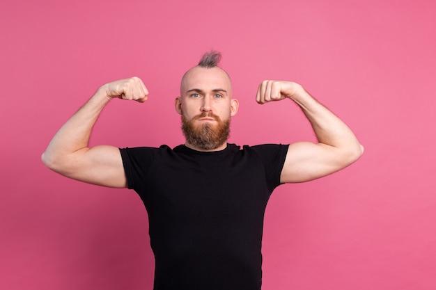 Starker europäischer mann auf rosa hintergrund, der muskeln zeigt