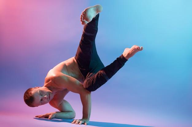 Starker flexibler mann, der morgenyogaübungen lokalisiert über neonwand tut