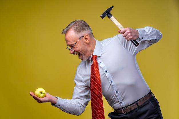 Starker geschäftsmann, der hemd hält, das hammer zeigt auf apfel zeigt
