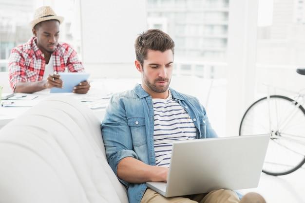 Starker geschäftsmann, der laptop auf couch verwendet
