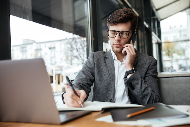 Starker geschäftsmann in den brillen, die durch die tabelle im café mit laptop-computer bei der unterhaltung durch smartphone und dem schreiben etwas sitzen