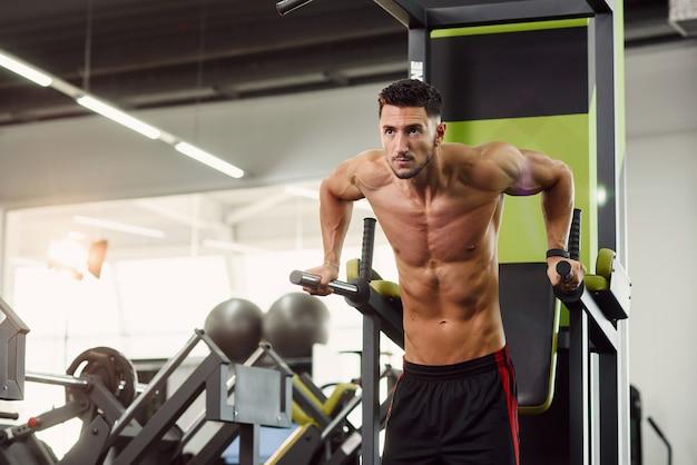 Starker gesunder mann, der liegestütze auf barren während des trainings im modernen fitnessstudio tut. sportliches und gesundes konzept. dolly schoss.