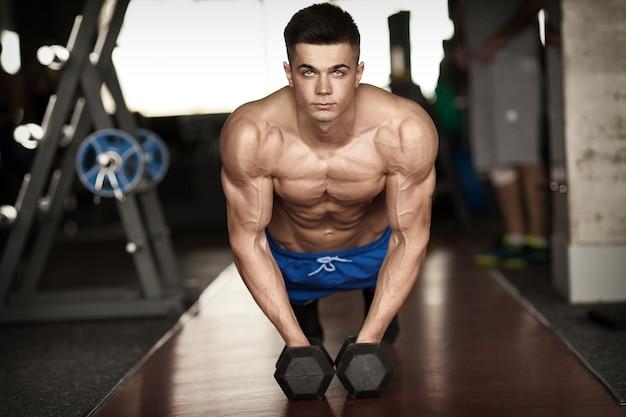 Starker, gutaussehender mann, der liegestütze auf hanteln in einem fitnessstudio als bodybuilding-übung macht und seine muskeln trainiert