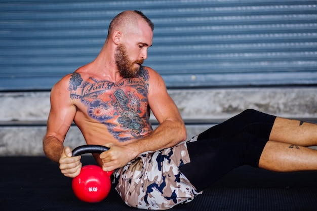 Starker gutaussehender mann sitzt auf dem boden und macht liegestütze mit hanteln in einem fitnessstudio