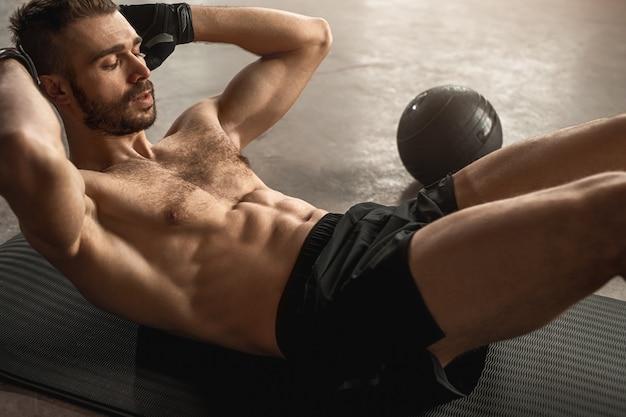 Starker hemdloser athletischer mann mit nacktem oberkörper, der während des intensiven trainings im fitnessstudio knirschen für die bauchmuskeln tut