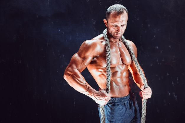 Starker hemdloser bodybuildermann, der mit seil aufwirft