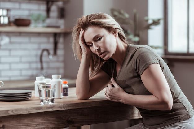 Starker herzschmerz. blonde depressive reife frau mit starkem herzschmerz, die pillen nimmt