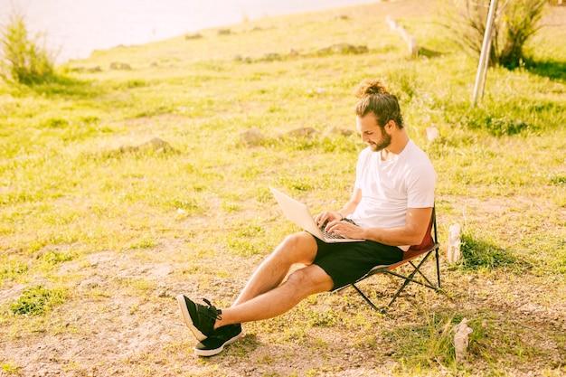 Starker hippie, der draußen mit laptop arbeitet