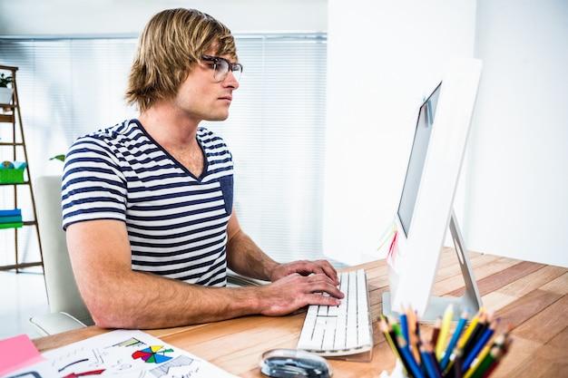 Starker hippie-geschäftsmann unter verwendung seines computers in seinem büro