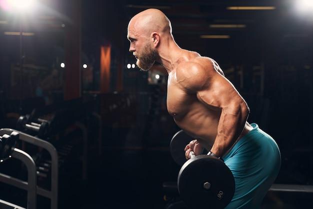 Starker junger athlet, der beim training mit einer langhantel mit gewichten im fitnessstudio hockt