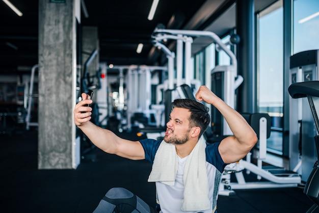 Starker junger athletischer mann, der selfie nach training nimmt.