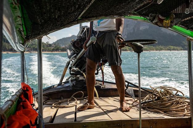 Starker junger fischer, der sein boot fährt und einen platz zum angeln sucht