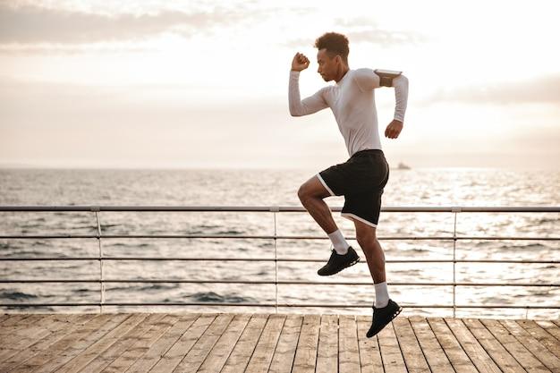 Starker junger lockiger dunkelhäutiger mann in schwarzen sportshorts und langärmeligem t-shirt springt und läuft draußen in der nähe des meeres