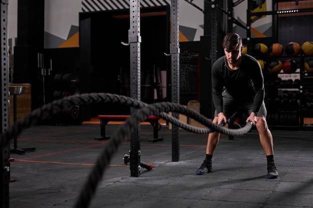 Starker junger mann, der mit kampfseilen im cross-fit-fitnessstudio trainiert. muskulöser kaukasischer sportler, der kreuzausflug mit seilen im fitnessstudio macht und allein körperliches training macht