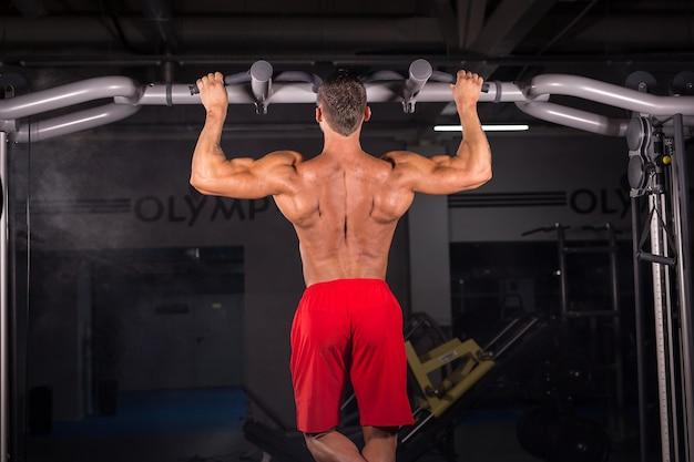 Starker junger mann, der pull-up-übung auf horizontaler stange im fitnessstudio tut