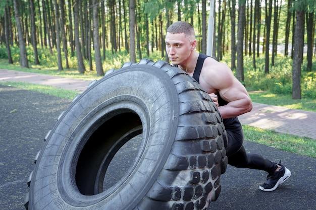 Starker junger mann, der reifen beim trainieren im freien leicht schlägt. crossfit.