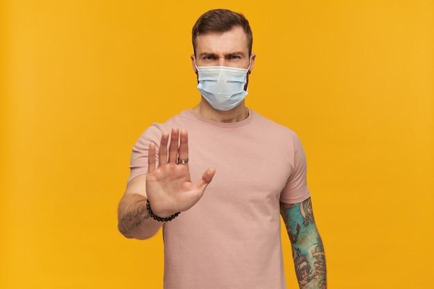 Starker junger mann im rosa t-shirt und in der virusschutzmaske auf gesicht gegen coronavirus mit bart und tätowierung, die stoppgeste durch seine hand über gelber wand zeigen