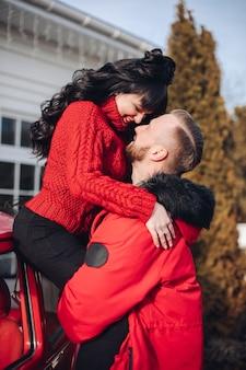 Starker junger mann im roten mantel, der eine herrliche smiley dame hält, während er sich auf ein rotes auto stützt