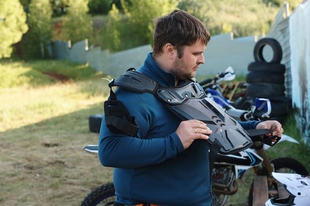 Starker junger mann mit stoppeln, die draußen stehen und motorrad-körperschutz tragen, während sie sich auf das rennen vorbereiten
