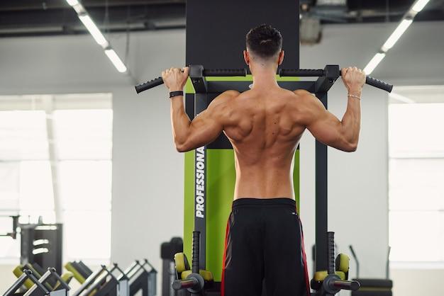 Starker junger mann zieht während des trainings im modernen fitnessstudio an der querlatte hoch. rückansicht.