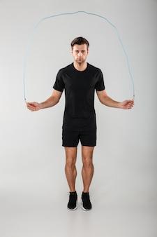 Starker junger sportmann, der mit springseil springt