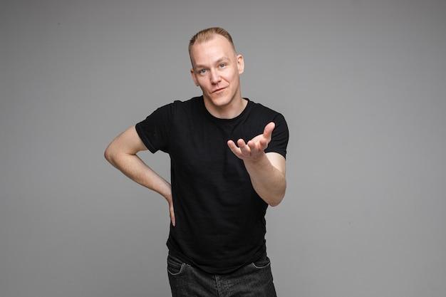 Starker kaukasischer mann mit kurzen blonden haaren, der ein schwarzes t-shirt und jeans trägt, versucht, etwas zu erklären