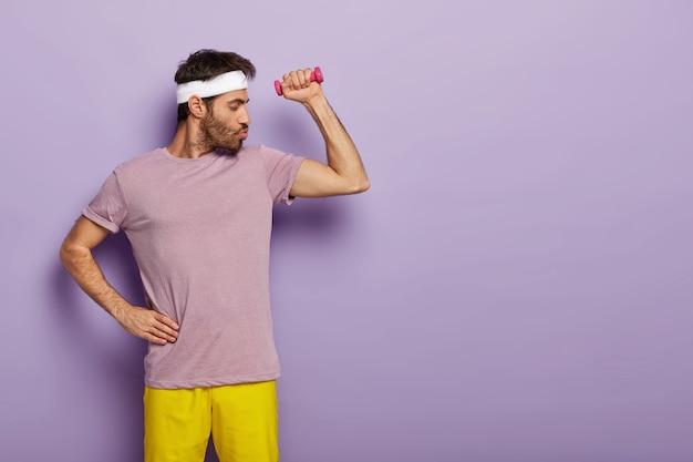 Starker, kräftiger mann mit dicken borsten, lässig gekleidet, hält eine hand auf der taille, macht übungen mit der hantel, trainiert regelmäßig