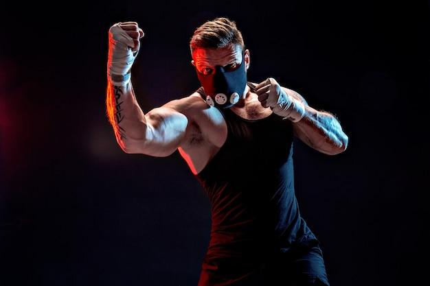 Starker männlicher athlet in einer schwarzen trainingsmaske auf einer schwarzen wand