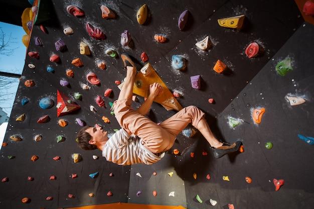 Starker männlicher bergsteiger auf der flusssteinkletterwand innen