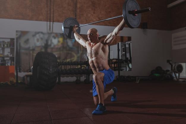 Starker männlicher crossfit athlet, der mit schwerem barbell trainiert