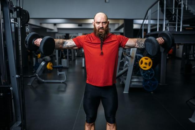 Starker männlicher gewichtheber, der übung mit hanteln im fitnessstudio macht.