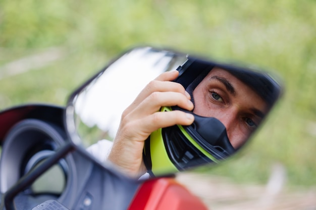 Starker mann auf tropischem dschungelfeld mit rotem motorrad