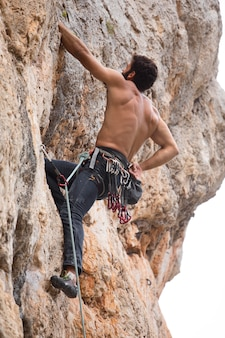 Starker mann, der auf einen berg klettert