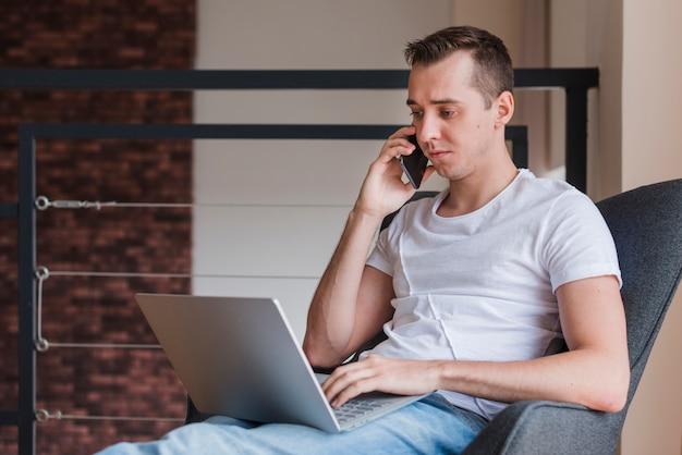 Starker mann, der auf smartphone spricht und auf stuhl mit laptop sitzt