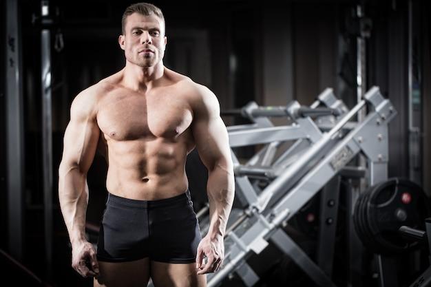 Starker mann, der bodybuilding in der turnhalle tut